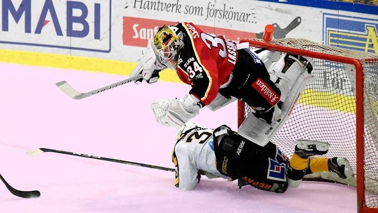 Två hockeyspelare vurpar på rosa is.