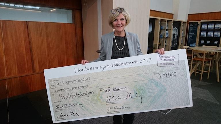 Anna-Lena Pogulis håller upp checken på 100 000 kronor.