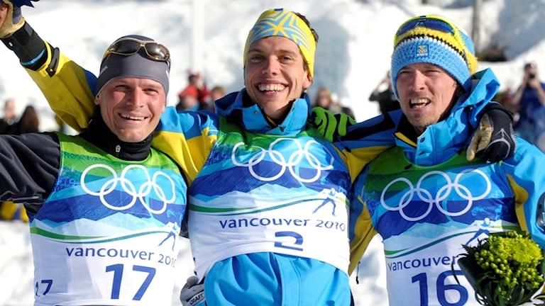 Marcus Hellner och Johan Olsson under blomsterceremonin efter guld och brons i tremilen i OS i Vancouver.