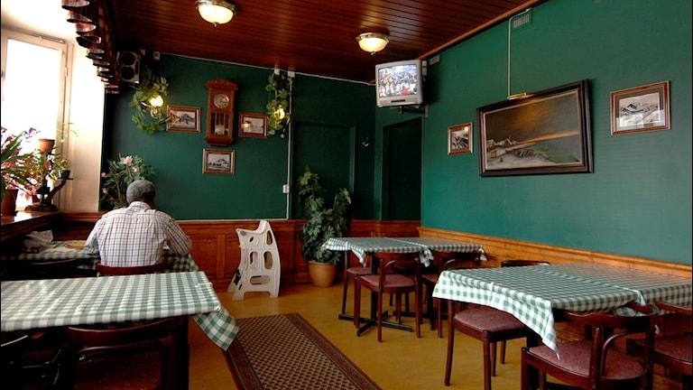 En ensam person sitter med ryggen mot kameran på en restaurang.