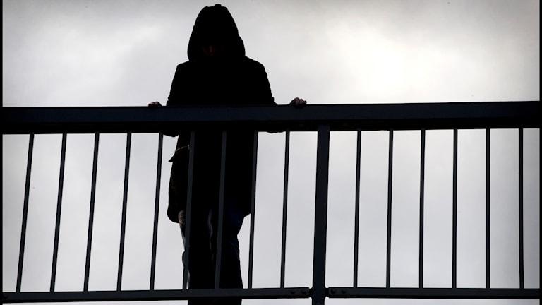 Deprimerad kvinnna på bro.