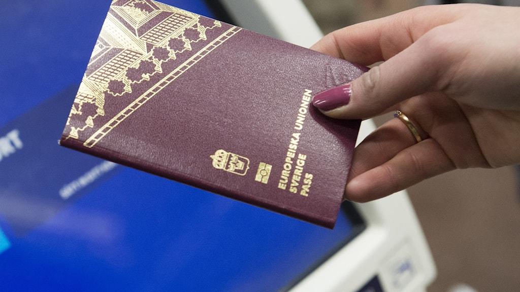 Ett svenskt pass framför en självbetjäningsautomat för incheckning på Stockholm Arlanda Airport.