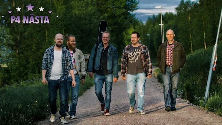 Bandet Julmas fem medlemmar går fram på en grusstig i en lummigt grön park.