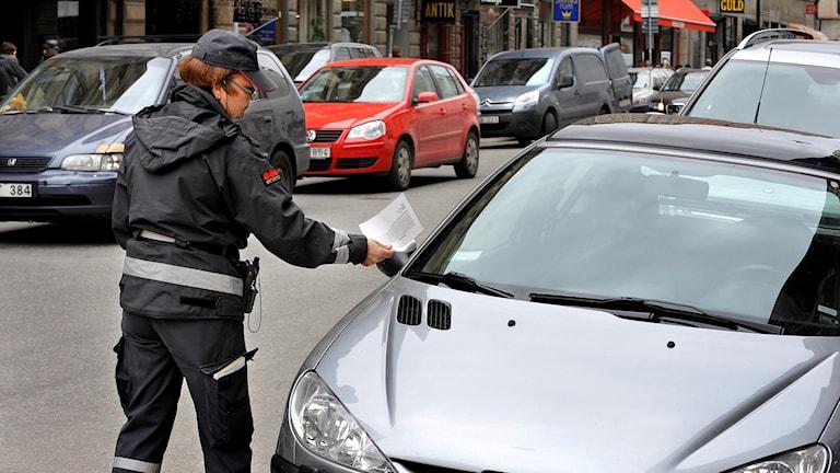 En parkeringsvakt lappar en bil.