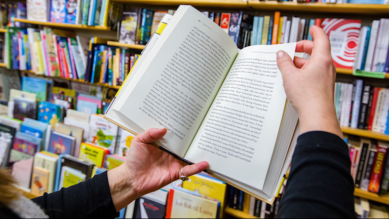 En person håller en öppen bok i händerna.
