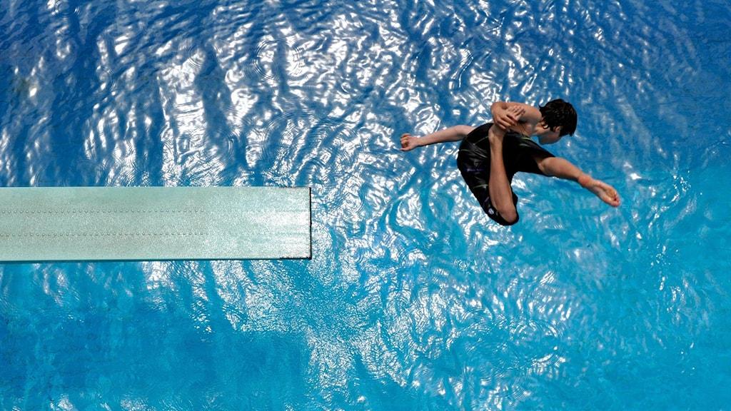 Pojke hoppas i swimmingpool från trampolin.