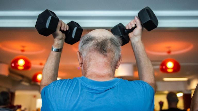 En äldre man håller i ett par hantlar ovan huvudet.