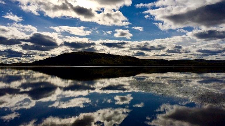 Spegelblankt vatten reflekterar himmel med solbelysta moln.