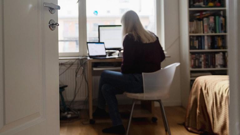 Kvinna som arbetar vid datorn hemifrån.
