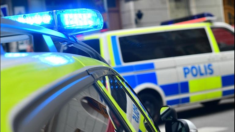 Polisbilar med blåljusen på.