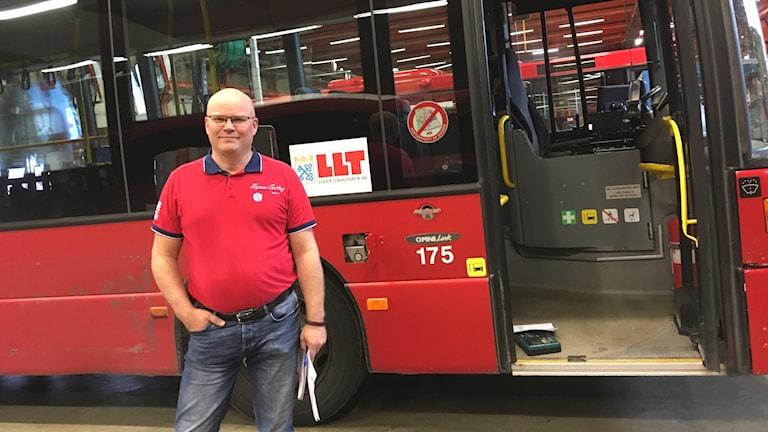 Torbjörn Niemi som är teknikchef på Luleå lokaltrafik står framför en av företagets röda bussar. Foto: Alexander Arvidsson/Sveriges Radio
