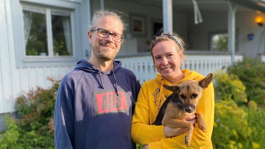 Erik Wernerlich och Matilda Mattsson Fröjd med sin hund framför sitt hus i Soukolojärvi