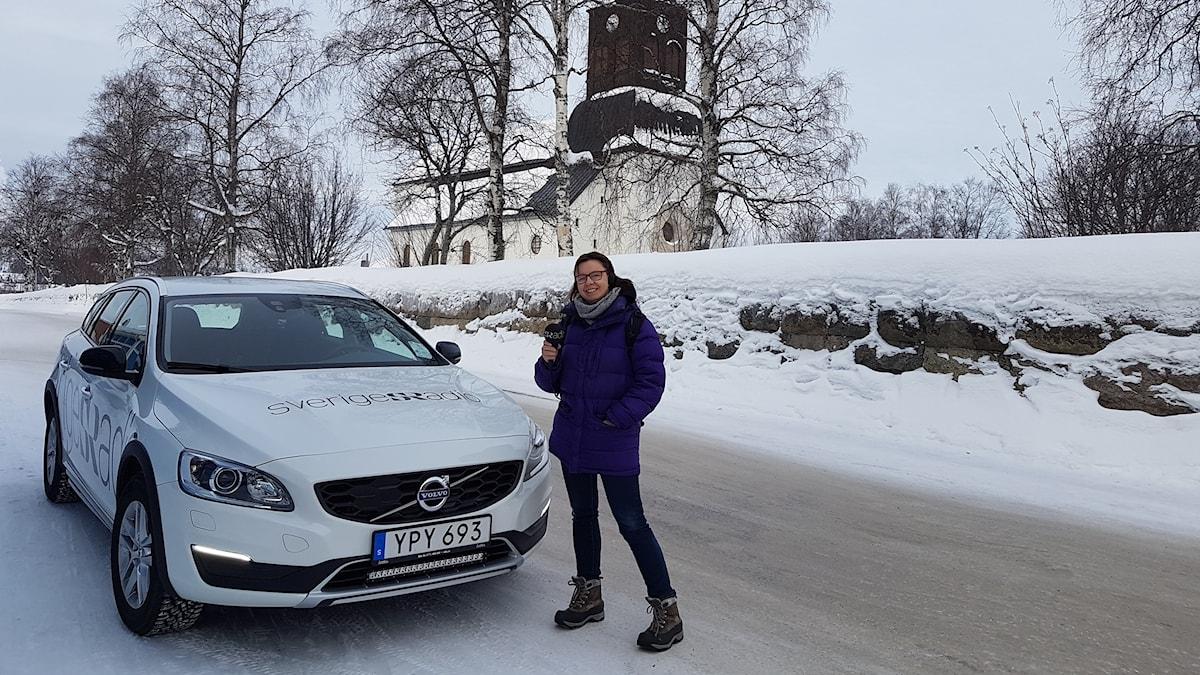 P4 Norrbottens Lena Callne vid Sveriges Radio-bilen framför Överkalix kyrka.