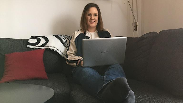 Linnea Eriksson sitter i soffan med datorn i knät.