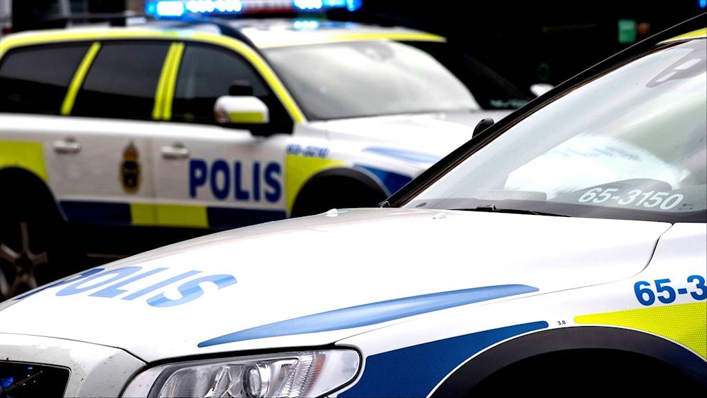 Polisbilar med blåljus.