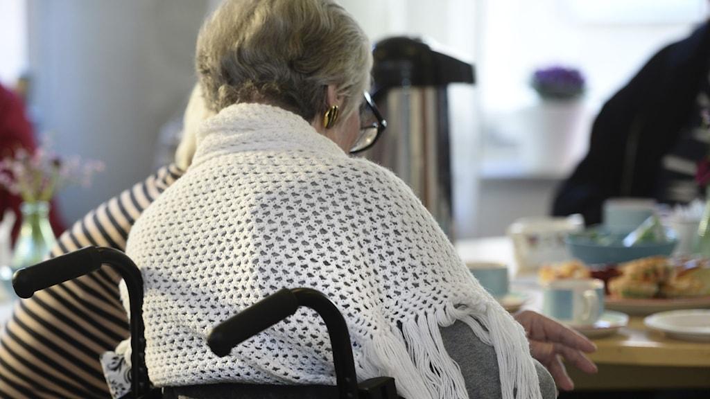 En kvinnlig pensionär med en sjal över axlarna sitter i rullstol.