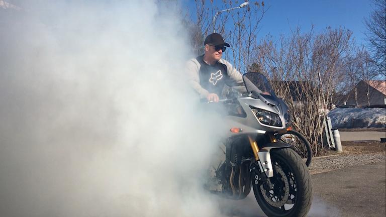 Man på motorcykel i avgaser.