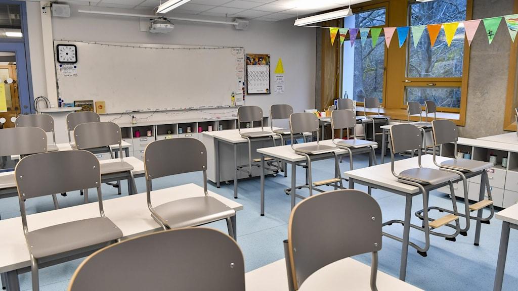Tomt klassrum med grå stolar.