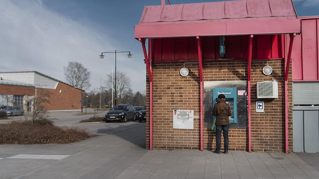 En person tar ut pengar i en bankomat, arkivbild.