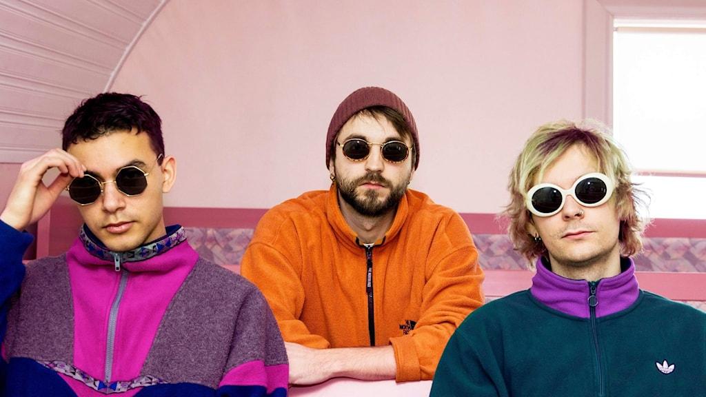 Isak Sidestam, Sebastian Hellis och Erik Antti sitter med solglasögon på inomhus med färggranna kläder.