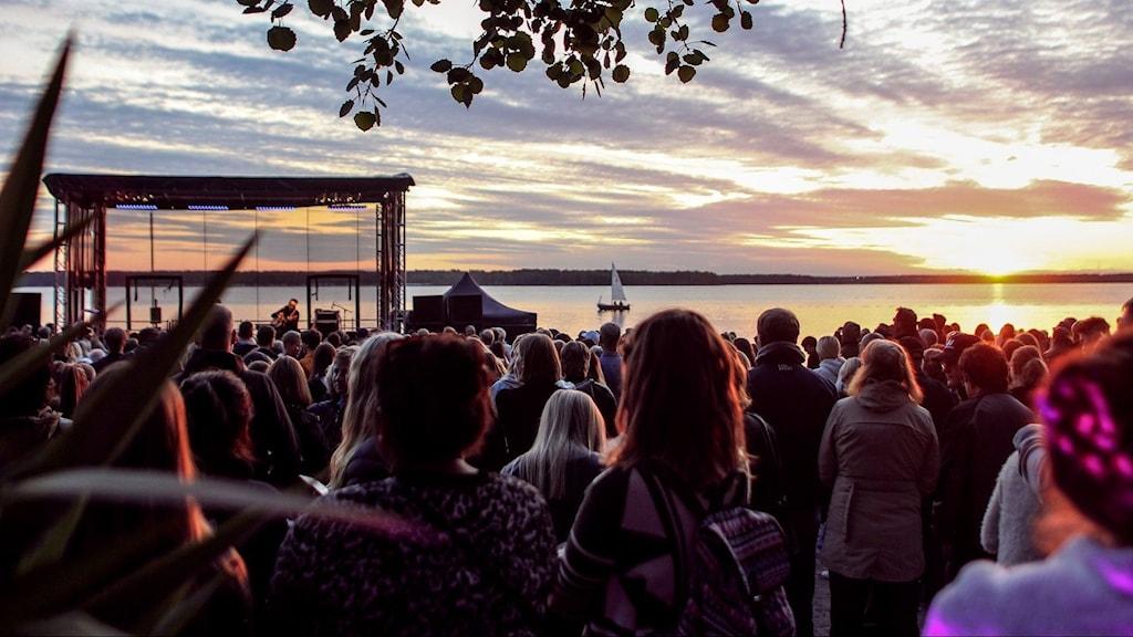 Scen och publik framför solnegång på Gültzauudden i Luleå under festivalen Musikens makt.