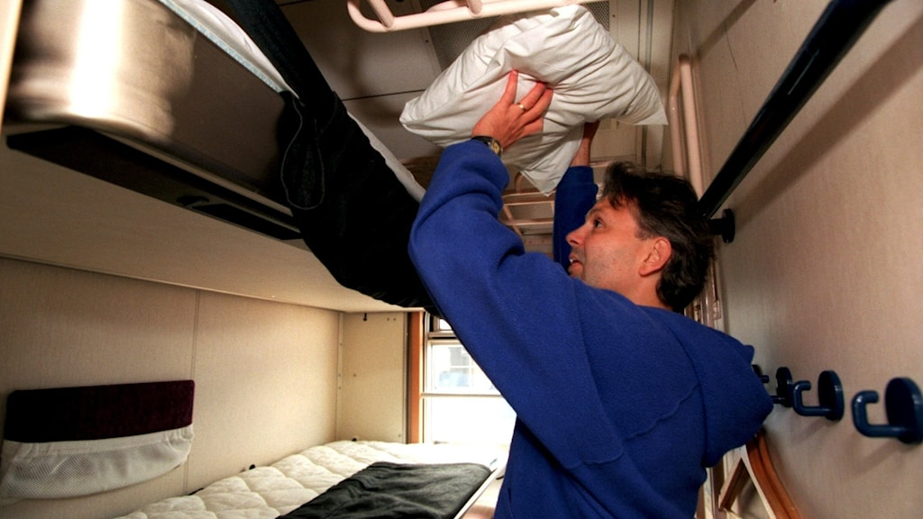 en man som stuvar in en kudde i förvaringsutrymmet på ett tåg i en sovkupe