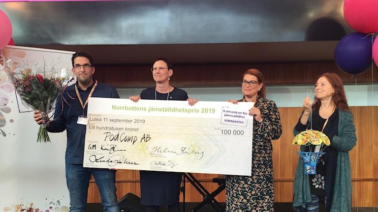 Vinnande Podcomd AB:s VD Peter Lundmark poserar med en check på 100 000 kronor tillsammans med tävlingens jury samt konstnären bakom konstverket som gavs som pris tillsammans med pengarna.