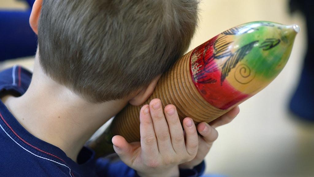 Pojke sedd bakifrån håller en så kallad gurka (musikinstrumentet) mot örat.