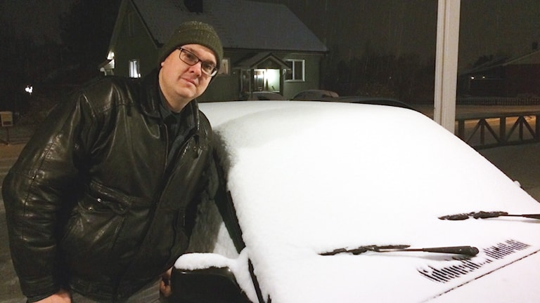 Pär Marklund står vid en översnöad bil.