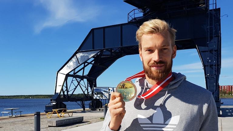 Anders Nilsson med VM-guldmedaljen i Luleås södra hamn med kranen i bakgrunden.