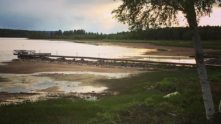 En strand med lågt vatten som inte når till bryggan.