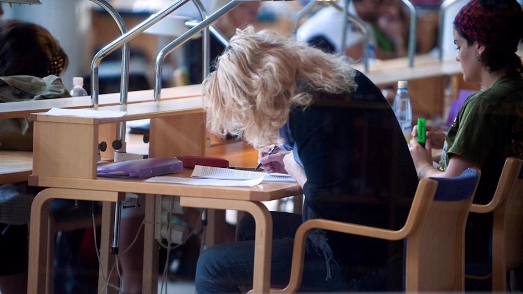 Kvinnliga studenter studerar i biblioteksmiljö.
