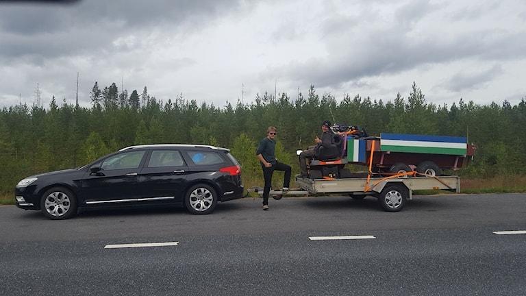 Gräsklipparen och vagnen hämtas upp med bil och släpvagn.