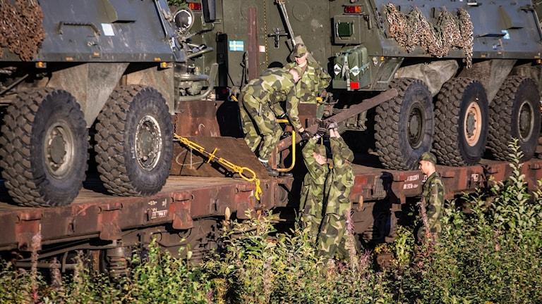 6 stycken soldater i kamouflagekläder arbetar med att surra fast Artilleribataljonens materiel på ett tåg för försvarsmaktsövningen Aurora 17. Foto: Cecilia Egefjord Ågren/Försvarsmakten