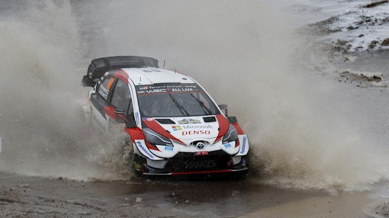 Rallybil kör genom vattenpöl.