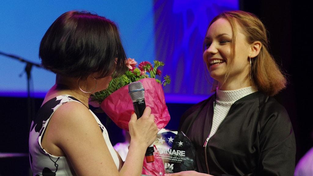 SaVe får blommor och plakett av programledare Lena Callne.
