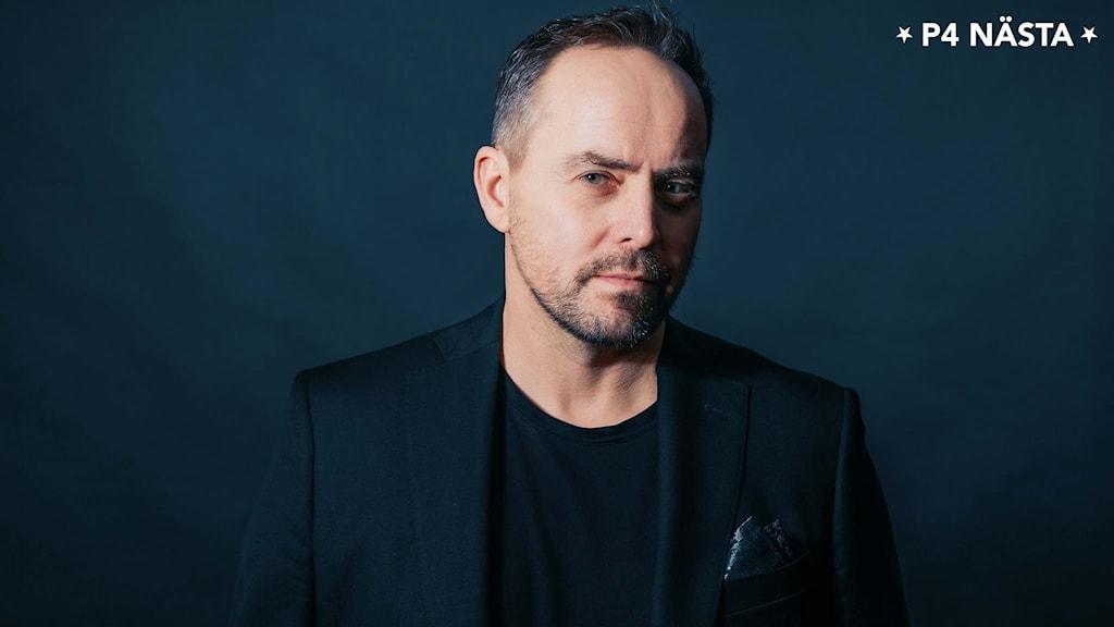 Porträttbild på Micke Holm med mörkblå bakgrund