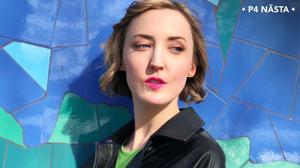 Porträttbild på Rut Sandbladh med blå och grön bakgrund.