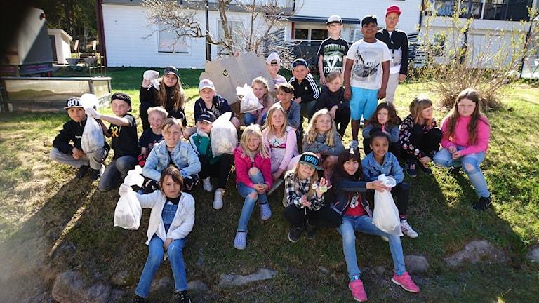 Eleverna i årskurs två på Hedskolan sitter i gräset och håller upp sina sopsäckar med skräp.
