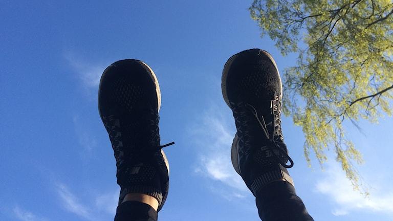 P4 Norrbottens Anneli Lindbäck lyfter skorna mot blå himmel. Foto: Sveriges Radio