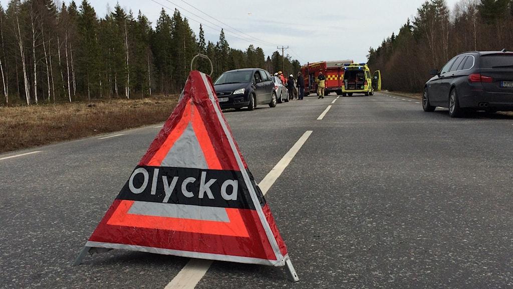 Trafikolycka med en varningstriangel i förgrunden och ambulans och bilar längre bort.