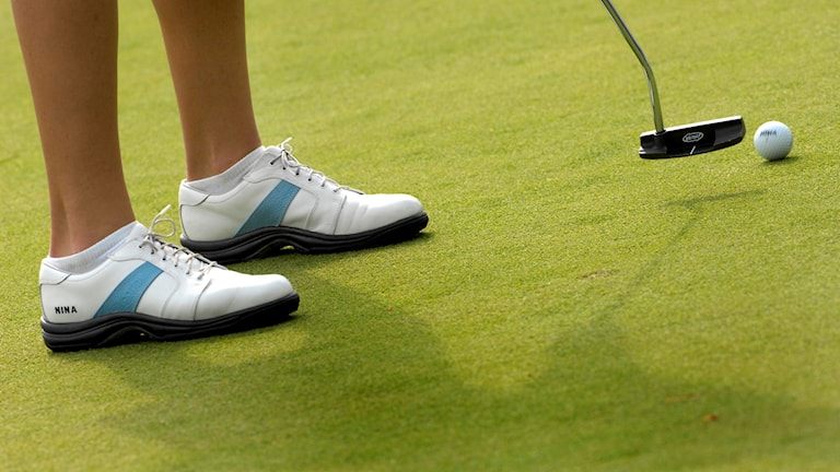 Golfspelare puttar.