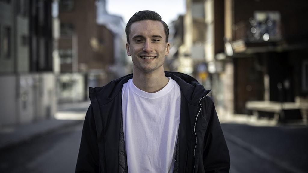 Skådespelaren Ivar Forsling står på en gata i stadsmiljö och tittar leende in i kameran. Han har på sig en vit t-shirt och en svart jacka.
