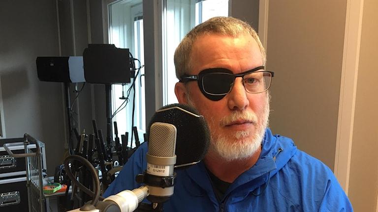 Cart Persson sitter framför en mikrofon i en studio.