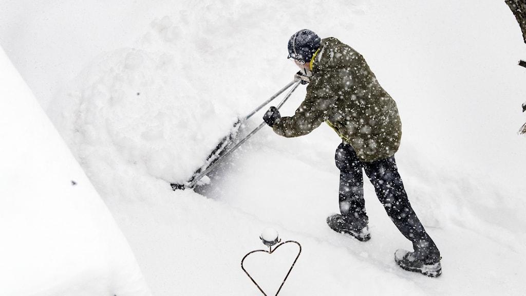 En man skottar snö.