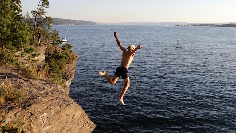 En pojke hoppar ut i havet från en hög klippa.