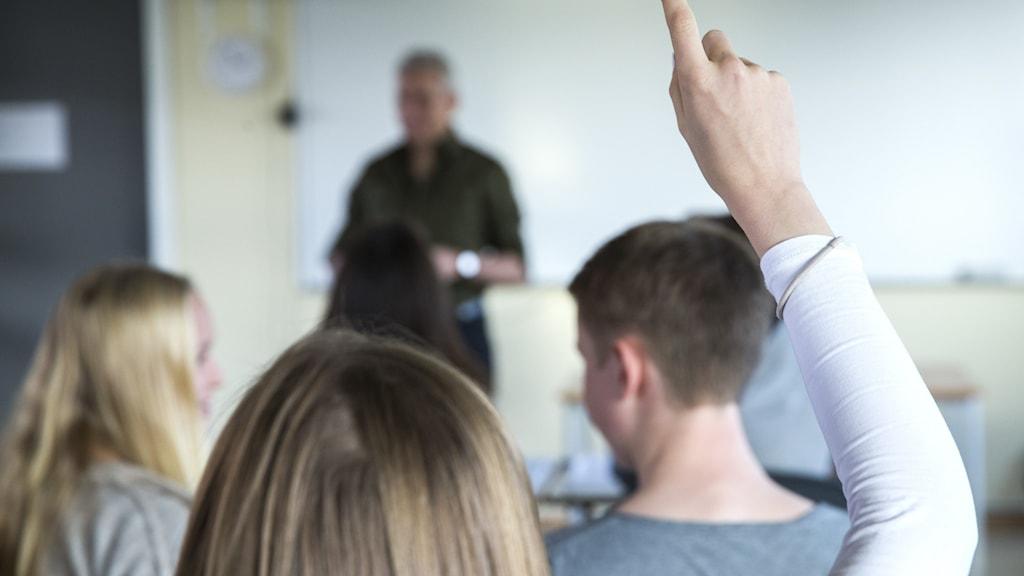 Klassrum på gymnasieskola, elev räcker upp handen med pekfingret höjt,