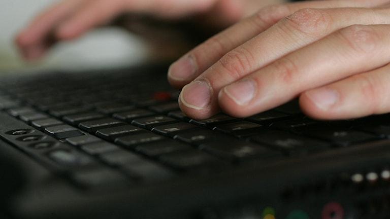 Fingrar på tangetbord till bärbar dator.
