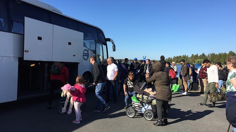 Asylsökande kliver på bussen i Haparanda för transport till Migrationsverket i Boden.