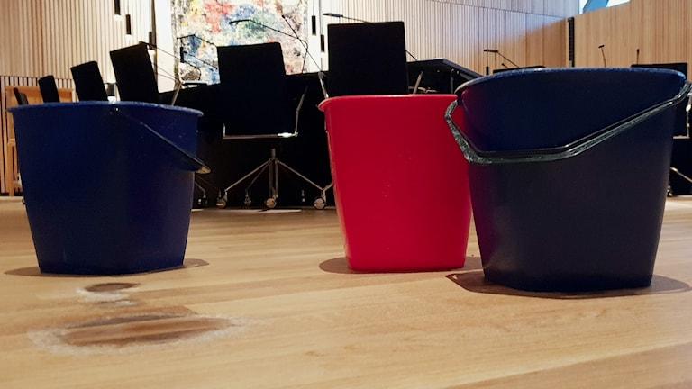Tre hinkar på golvet i kommunfullmäktiges mötesrum i Kirunas nya stadshus.